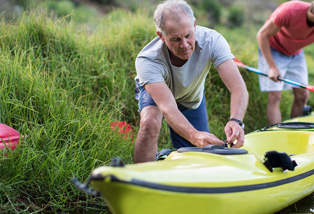 Elderly man rigging up a kayak with a friend