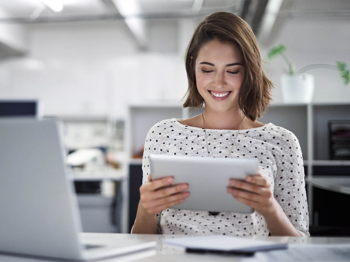 A young woman holding and looking at a tablet in a modern office