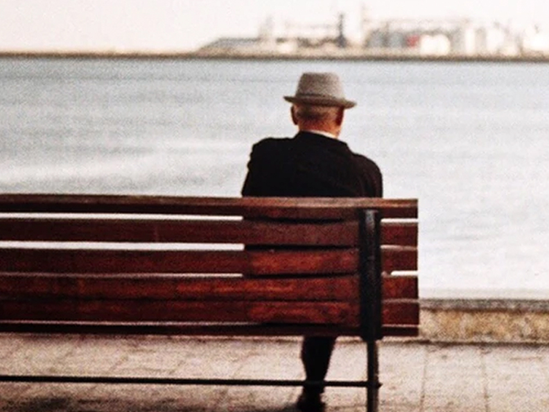 Elderly man with hat sitting on bench
