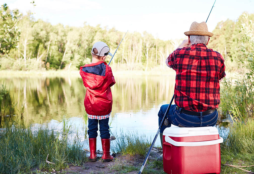 Grandfather and grandson fishing on a lake.