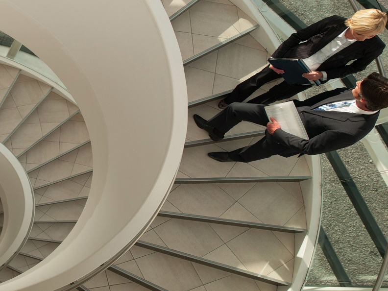 Business people stand on a spiral staircase
