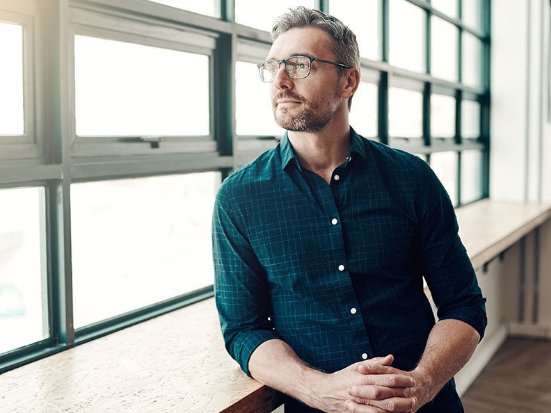 A middle aged man with glasses in smart casual clothing looking out a window of a modern office
