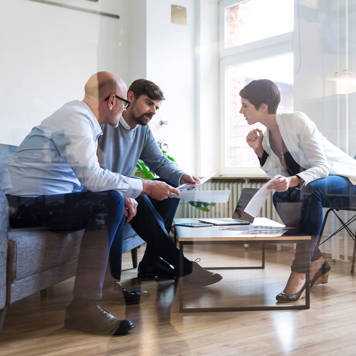 Three colleagues, two male and one female sitting in a casual boardroom having a meeting during the day.