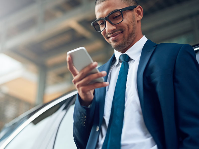 Shot of a young businessman using his phone while standing outside leaning against a car. He's wearing a suit.