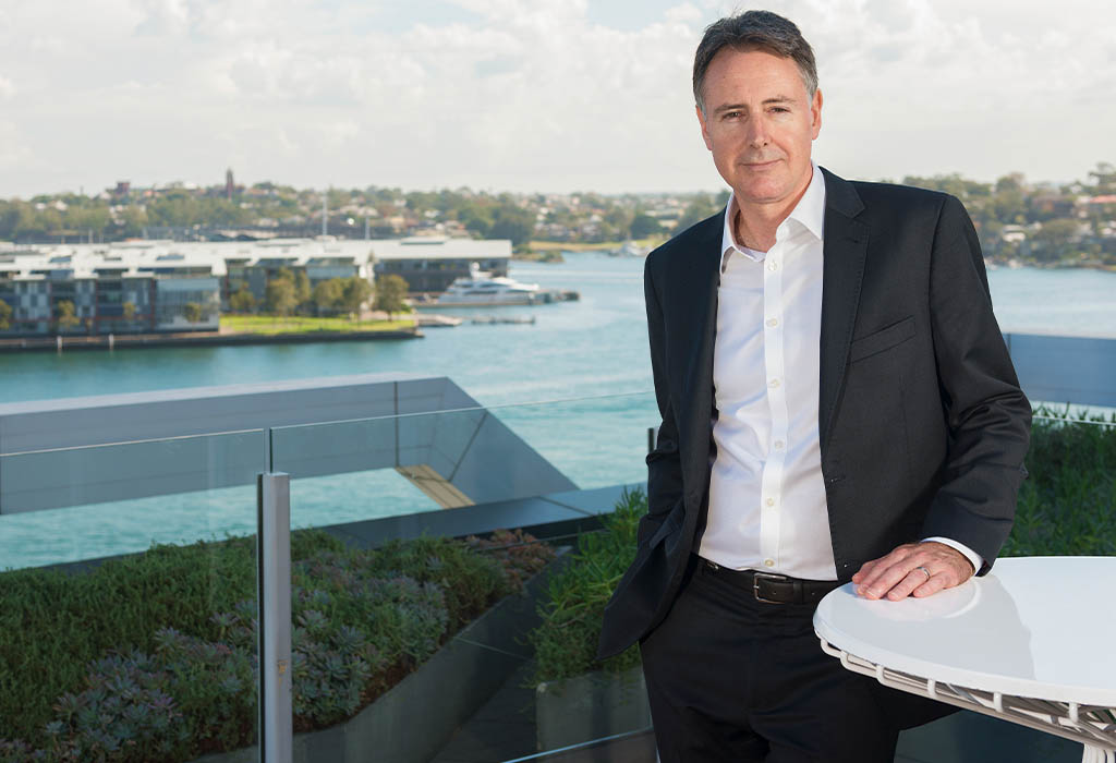 A business man in a suit standing outside on an office rooftop with a hand on a table. Macquarie employee - David Barrett