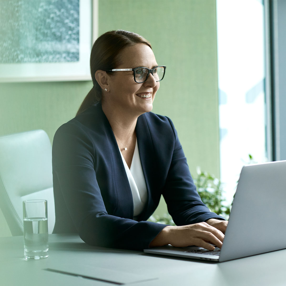 A businesswoman with glasses sitting at a desk working on laptop and smiling
