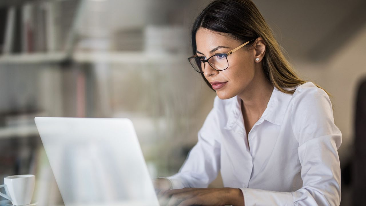 A mid-shot of a young business woman with glasses on working on a laptop in a quiet looking office.