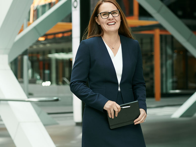 A businesswoman with glasses standing outside a Macquarie office. Macquarie - Julia