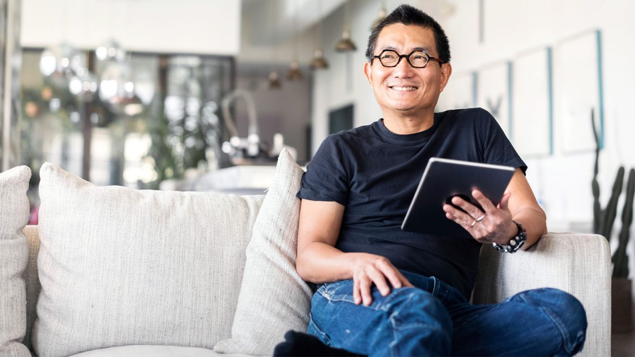 Mature aged Asian man sitting on sofa with a digial tablet in hand and smiling