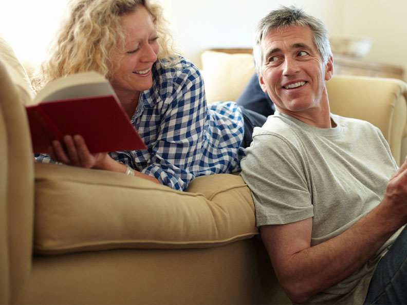 A couple looking at eachother as they read books together in their lounge room on their couch in their home. A man is using a tablet and a woman is holding a hardcover book.