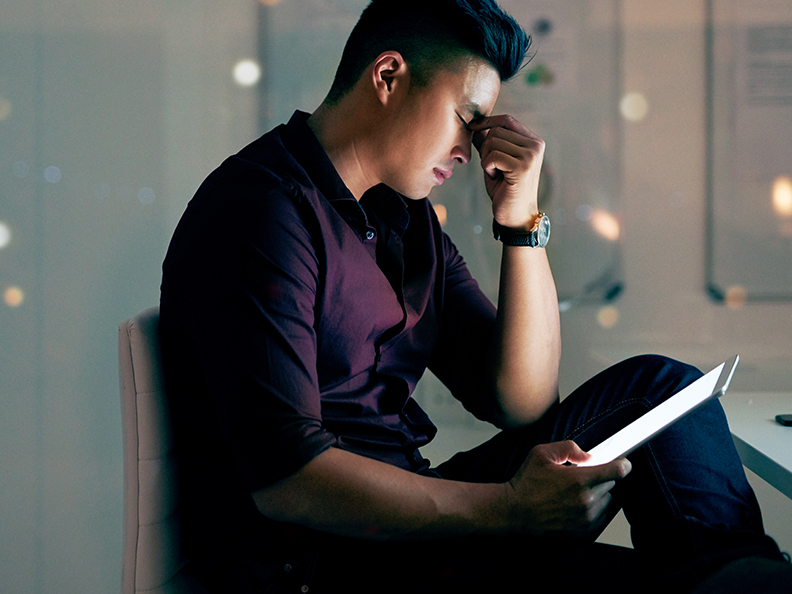 Shot of a young asian man looking stressed while using a digital tablet at night in a modern office
