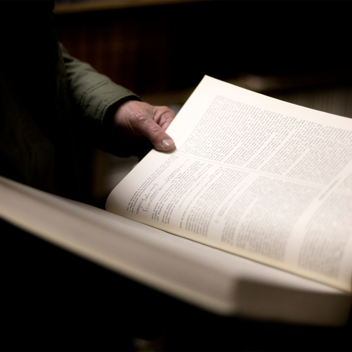 A person holds a large textbook in one hand in a dimly lit room.