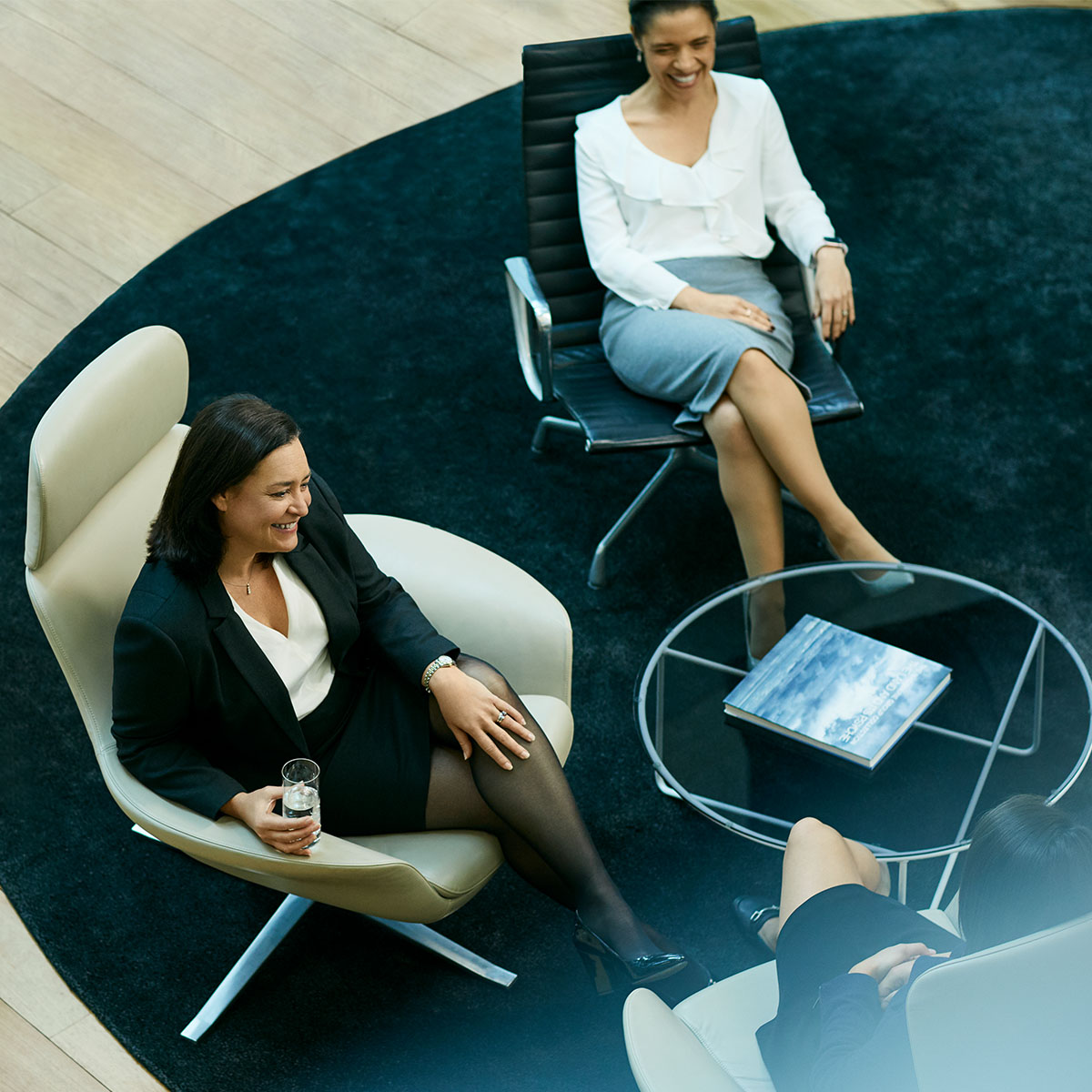 A birds eye shot of 3 business woman sitting at a small black round coffee table. Macquarie - Sherise Bianca