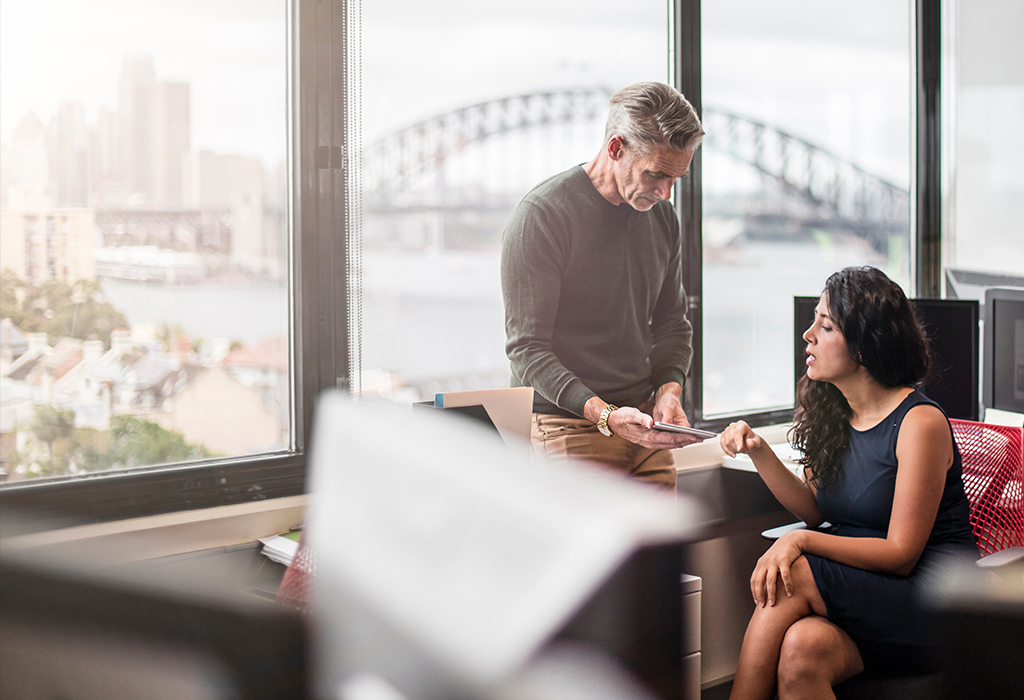 Two coworkers chatting over paperwork with Sydney Harbour Bridge in the background