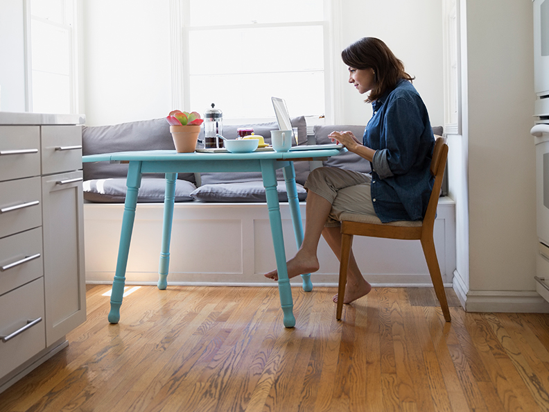 Woman on laptop in her kitchen