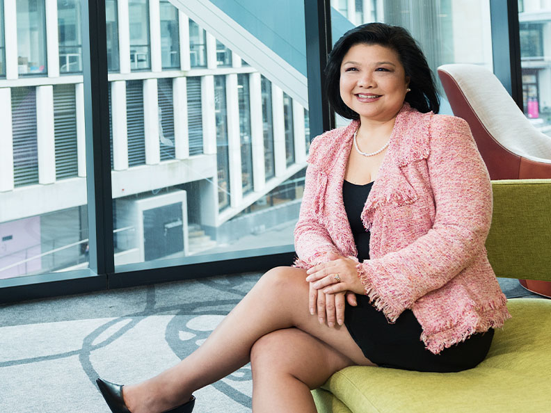 A business woman sitting in a modern office in a pink blazer and smiling. Macquarie - Margaret
