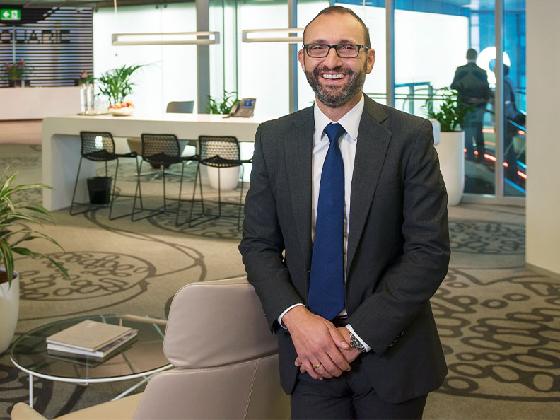 Professional man in a suit smiling in the lobby of a Macquarie office.