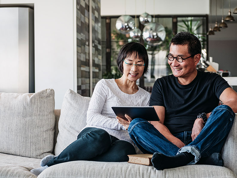 Mature woman and man using digital tablet at home in living room, talking online, facetime, social media