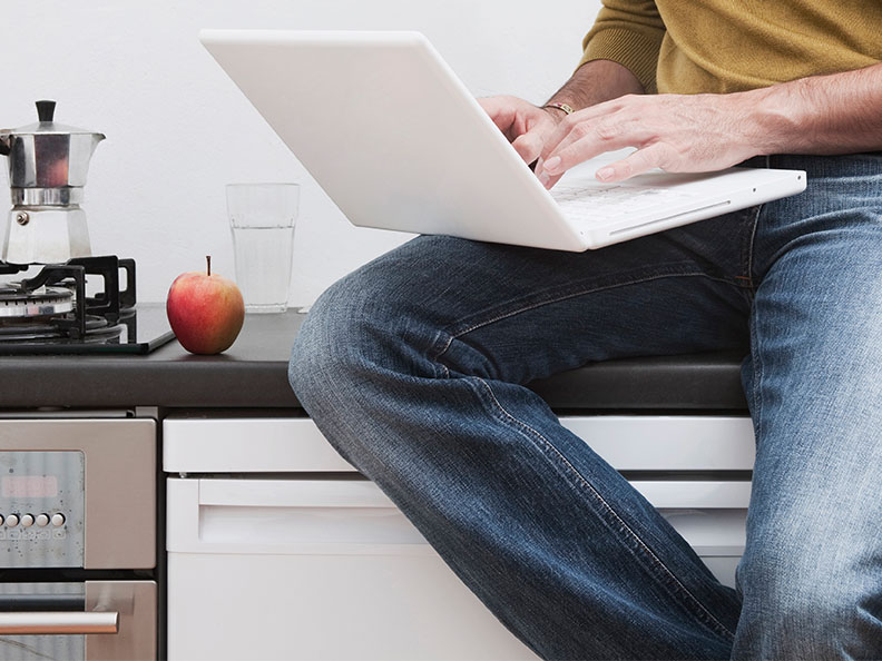 A lower half view of a person sitting on a kitchen counter with their laptop open.