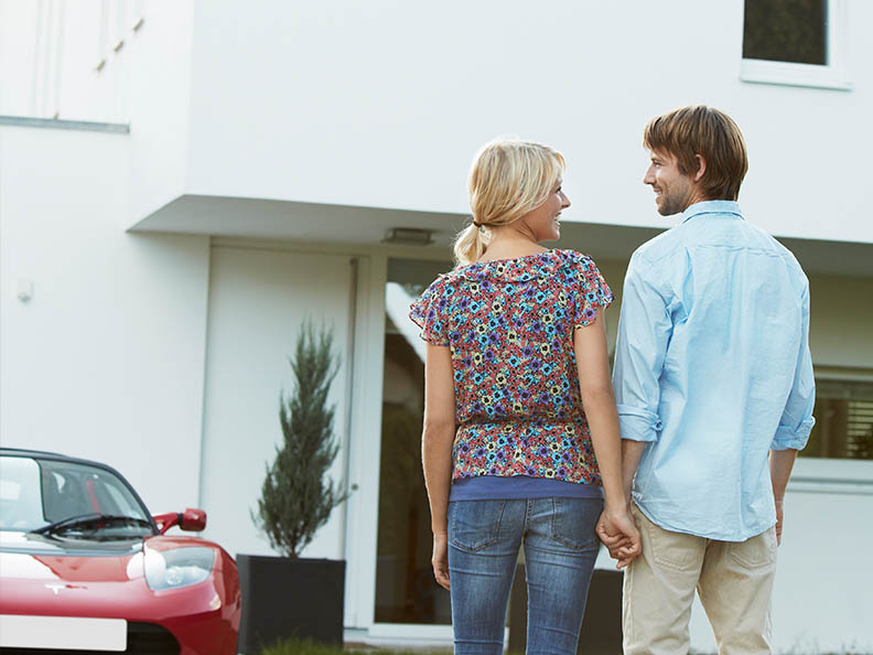 Couple in front of house + electric car