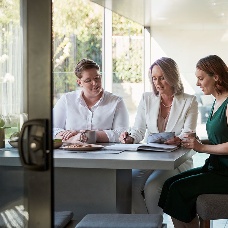 Couple sitting their professionally dressed broker in a well lit house. Macquarie customer - Georgina, Celeste, and Deanna