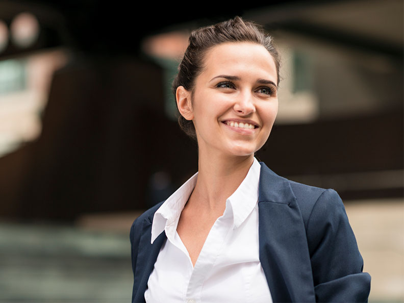 A close up shot of a young business woman looking to the left while outside