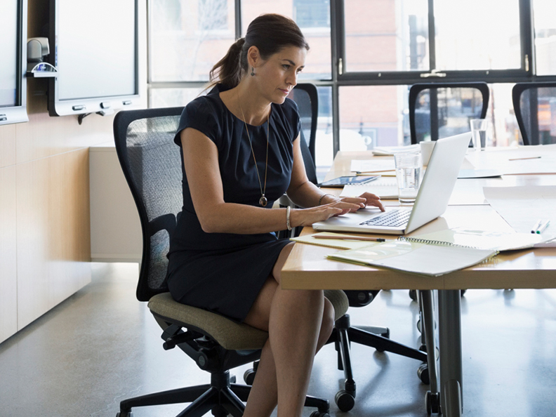 Businesswoman working at laptop in conference room