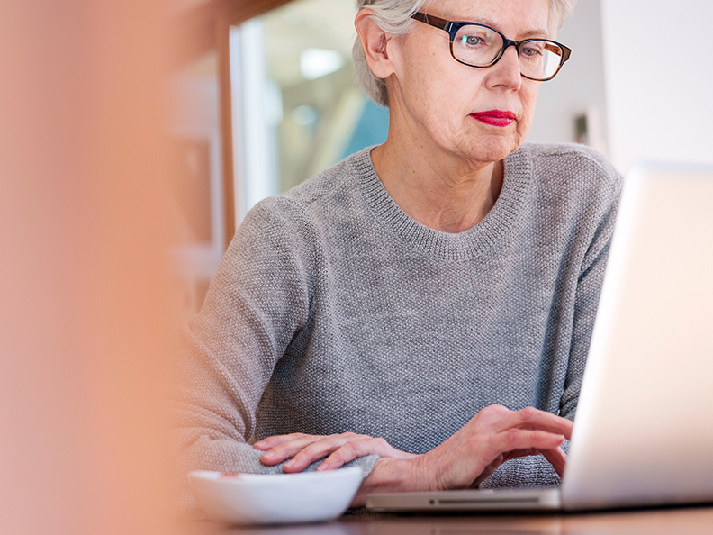 Mature woman with glasses on laptop in casual setting.