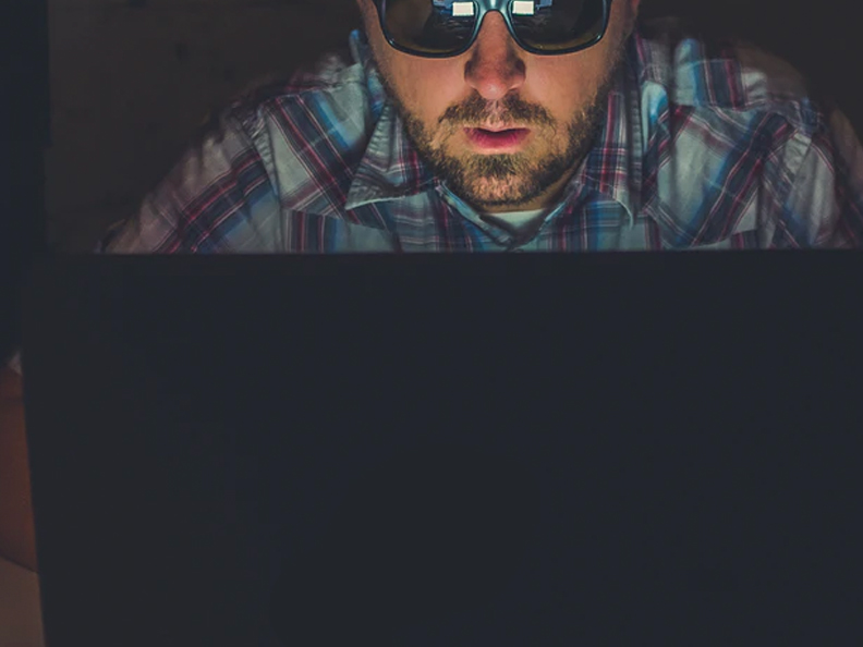 Man with sunglasses on laptop in dark room