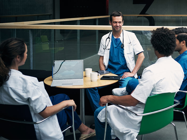 Shot of a group of medical staff seated around a table drinking coffee and having a discussion inside a hospital