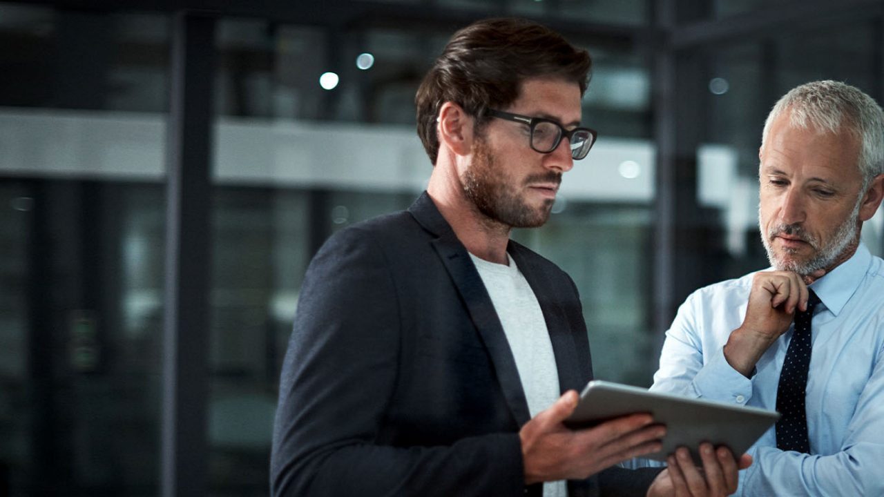 A mid shot of two business men looking at a smart tablet together in the office at night. One man is middle aged and the other is younger.