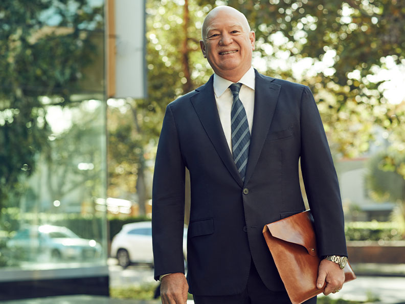 A businessman in a suit standing outside smiling as he holds some documents in his hand on a sunny day. Macquarie - Craig