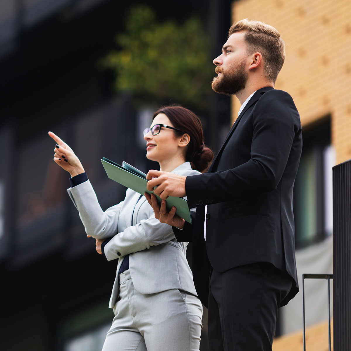 A business woman points something out to her colleague outside. Her colleague is holding some documents.