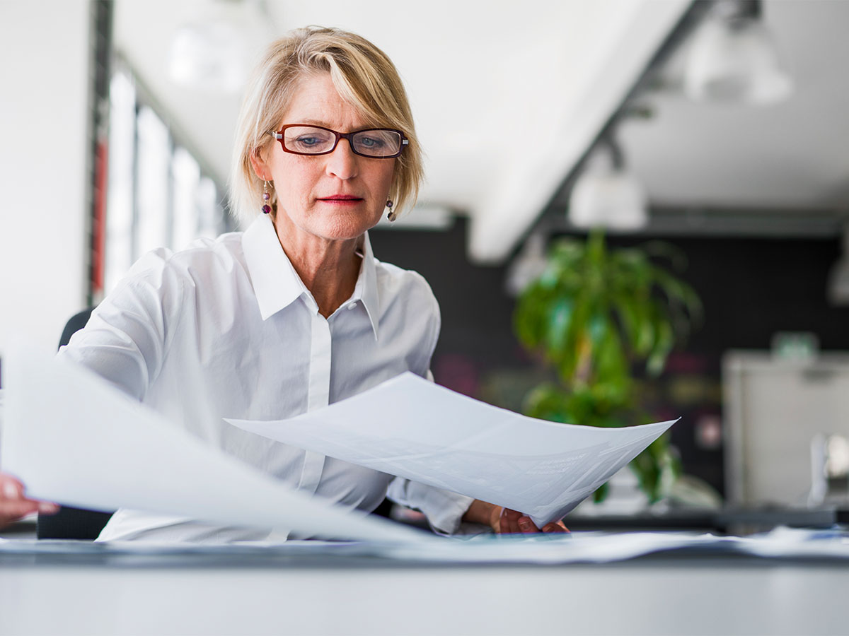 A mature aged business woman with glasses holding paper in each hand in a well lit office space
