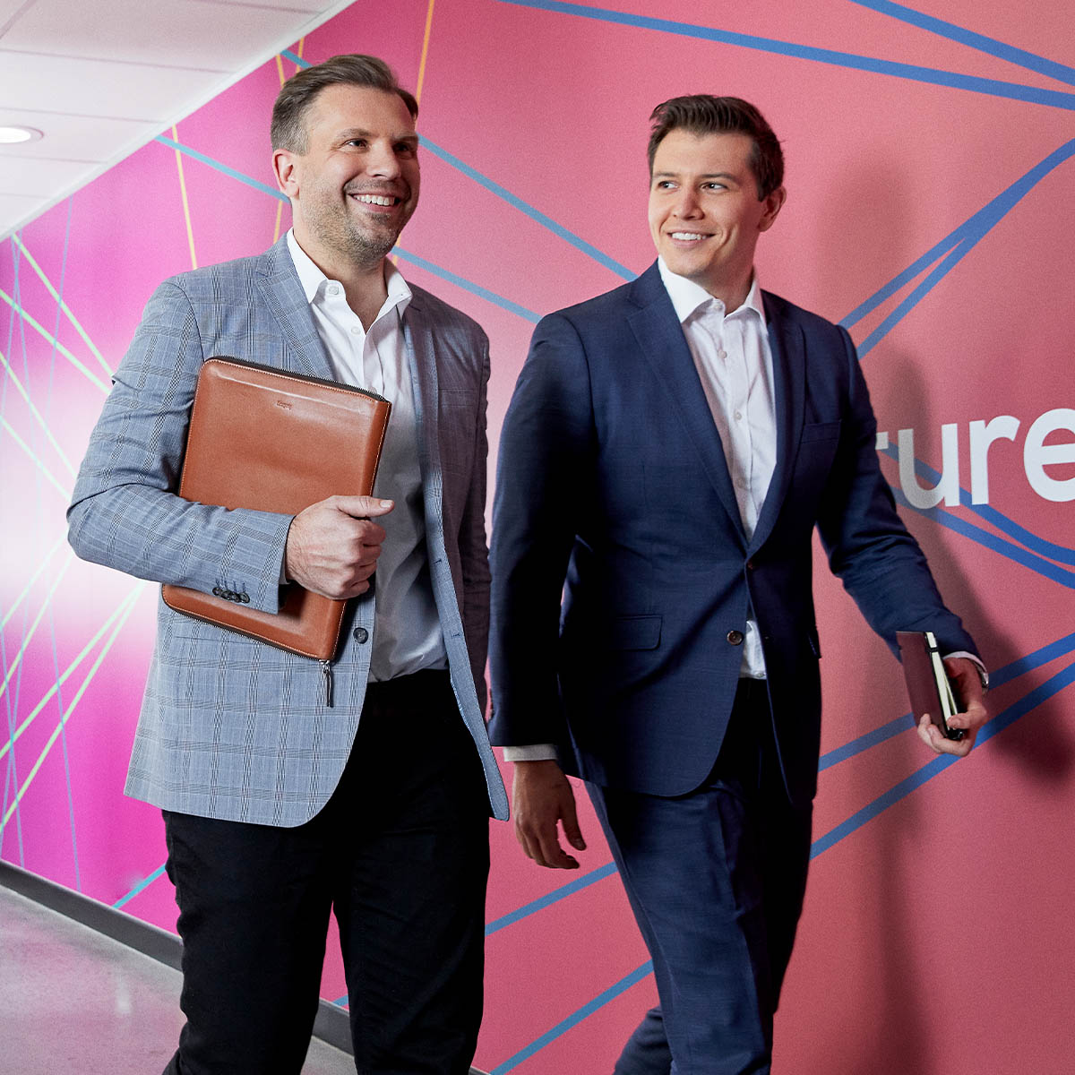 Two men in suits walking down a corridor with a colourful wall behind them. Macquarie customer - ReadyTech