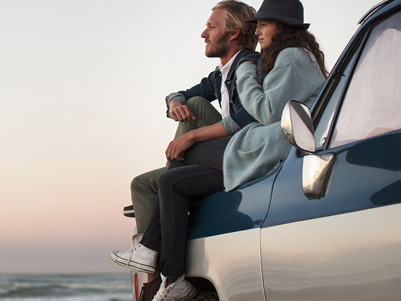 Couple on car looking out to a sunset.