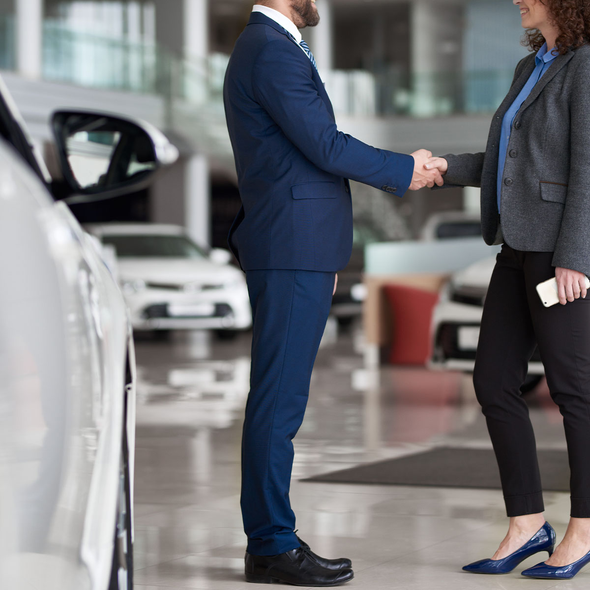 Businesswoman buying car in automobile dealership and shaking hand of manager as symbol of successful deal