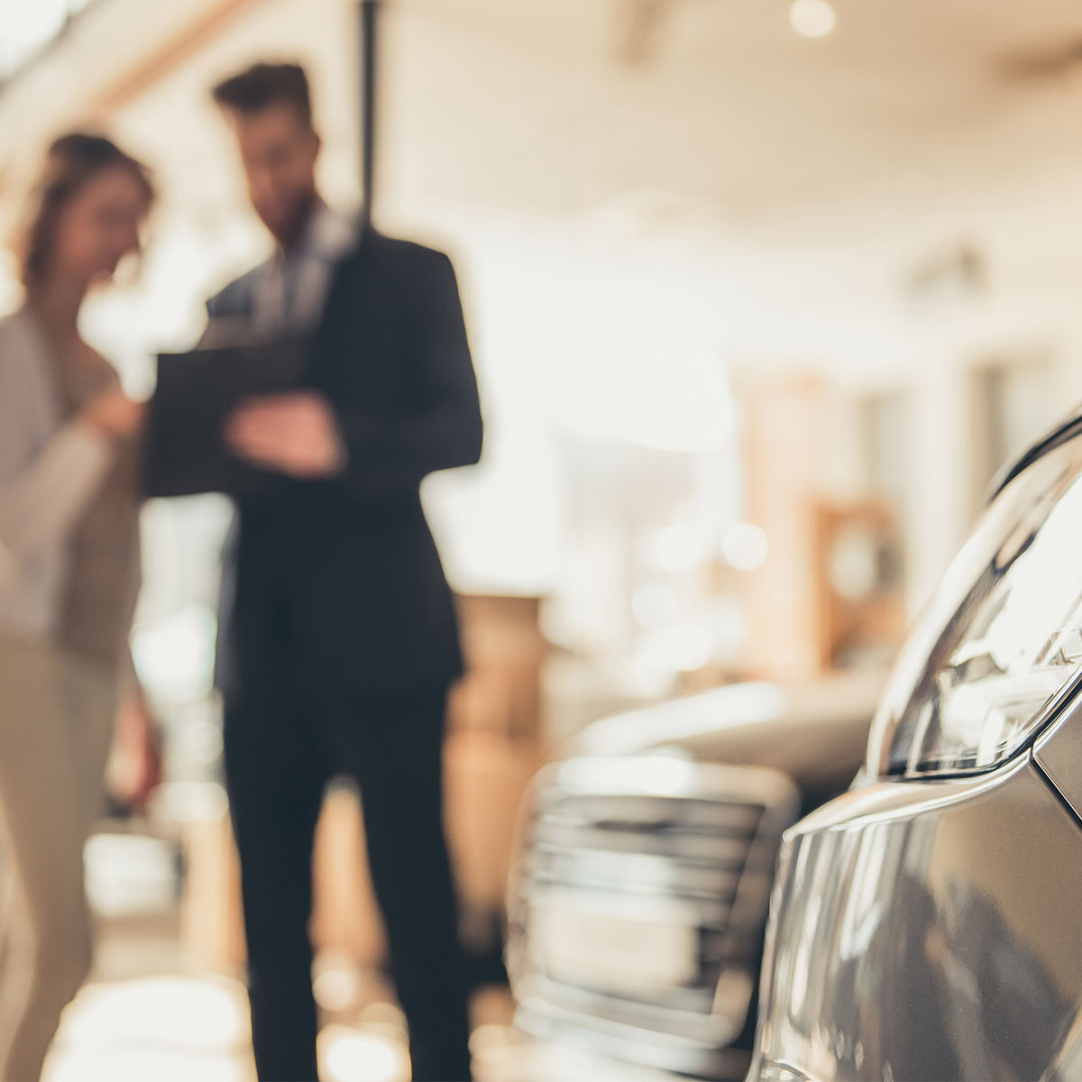 Young woman is talking to a bearded sales manager while choosing a car in dealership. Car is in focus and people are blurred in background.