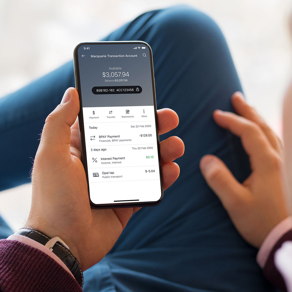 A man lounging back and using his smart phone with the Macquarie bank app open on a transactions screen
