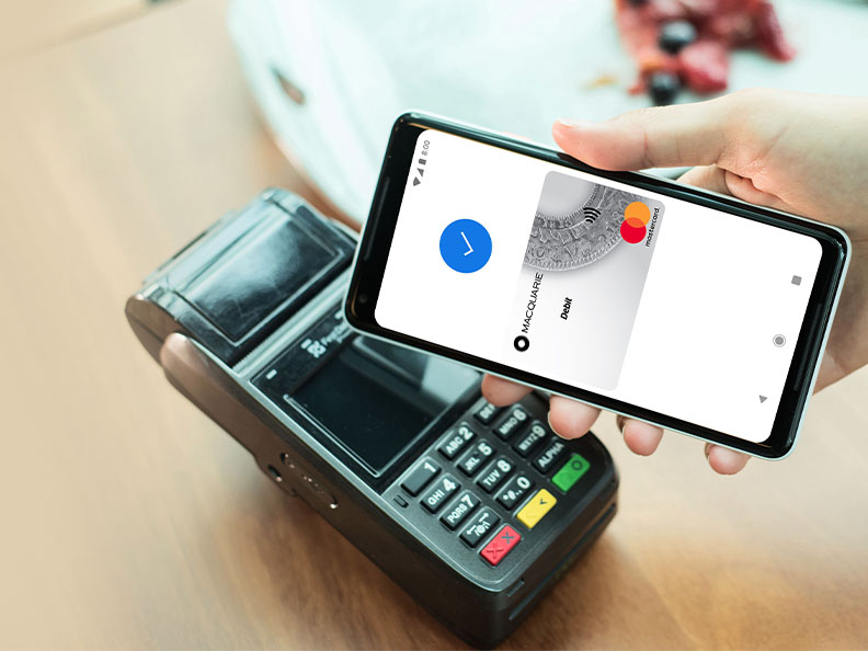 A phone showing a successful Macquarie Google Pay over a Eftpos terminal