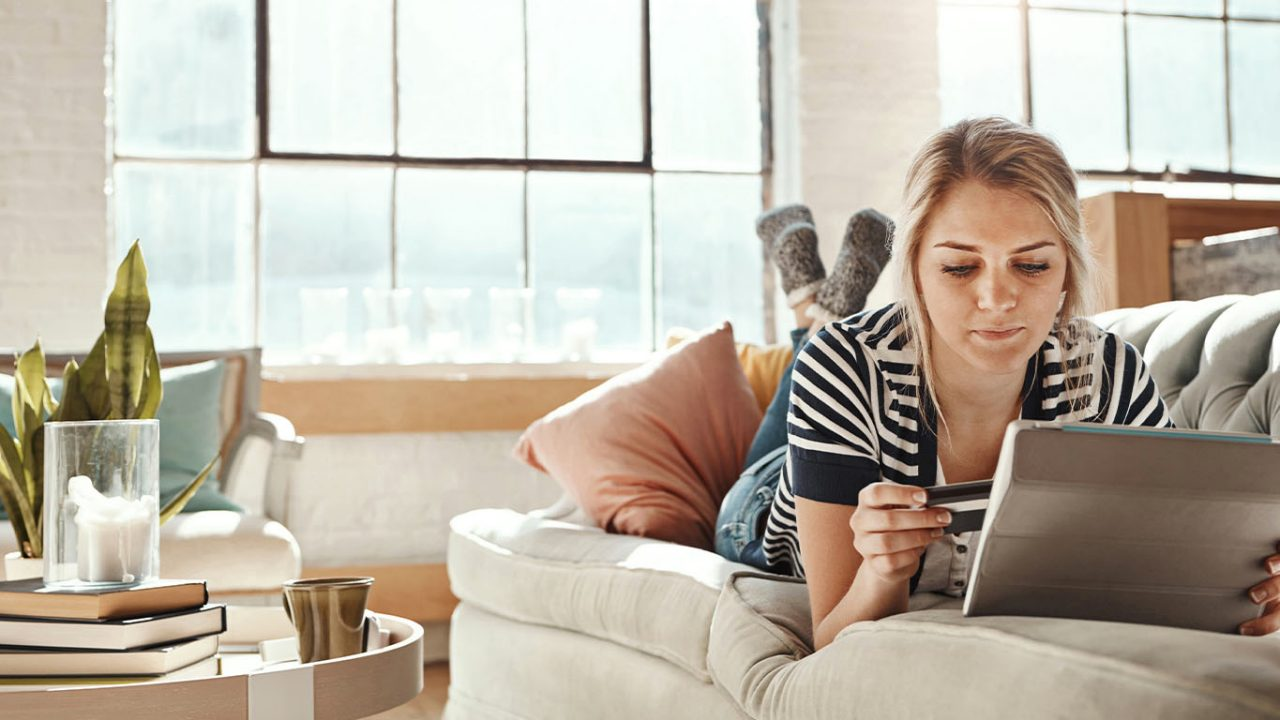 Shot of a young woman relaxing on the sofa and using a credit card with a digital tablet