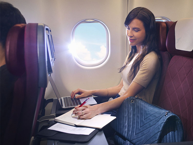 A woman working on her laptop and writing in a notebook on a Qantas airliner plane