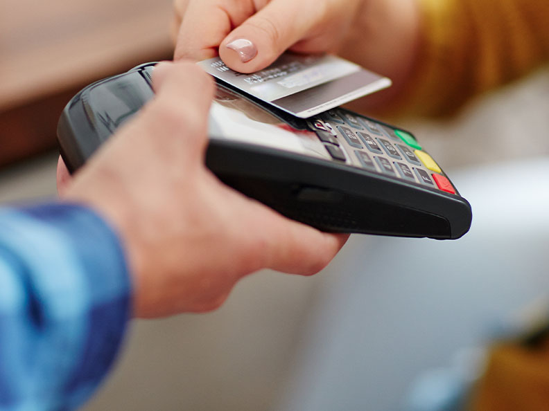 Close-up of unrecognisable customer choosing contactless payment using credit card while wait staff accepts payment over nfc tap pay pass technology