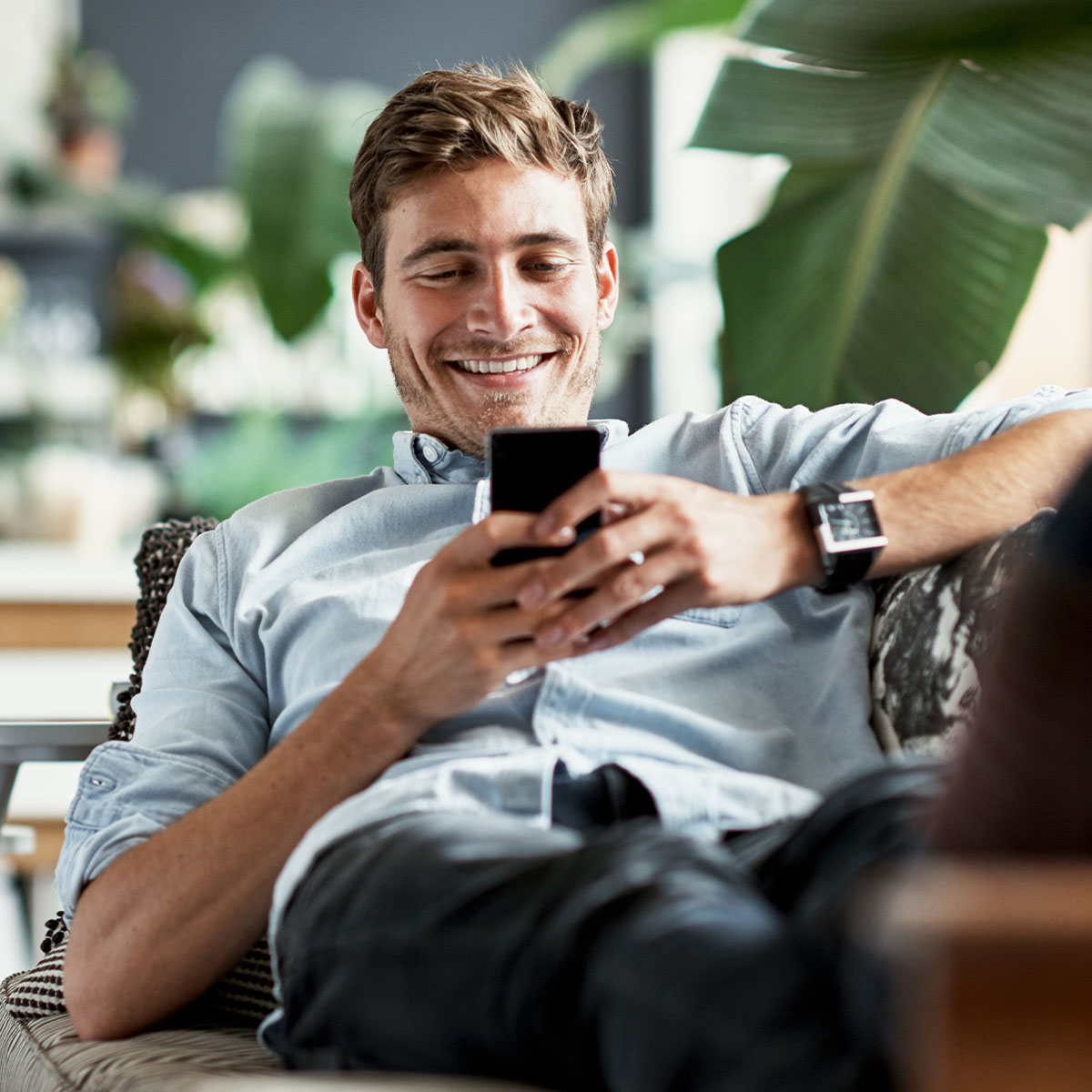 Man lounging dressed smart casual on a couch on his phone and smiling