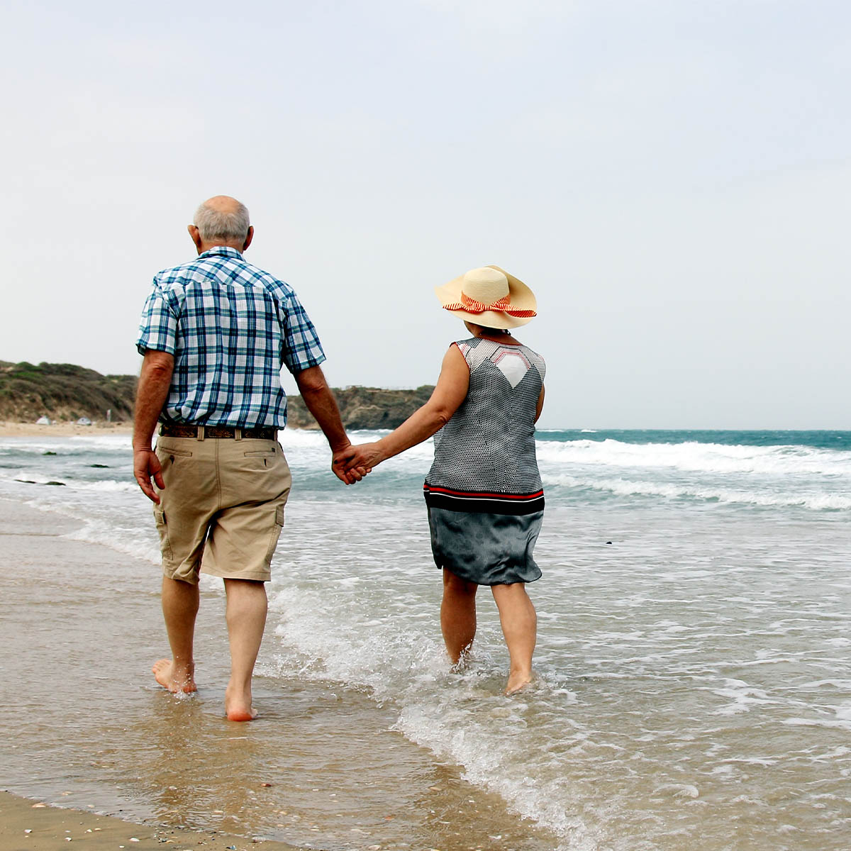 A mature aged couple walks along the water at the beach during a sunny day while holding hands.