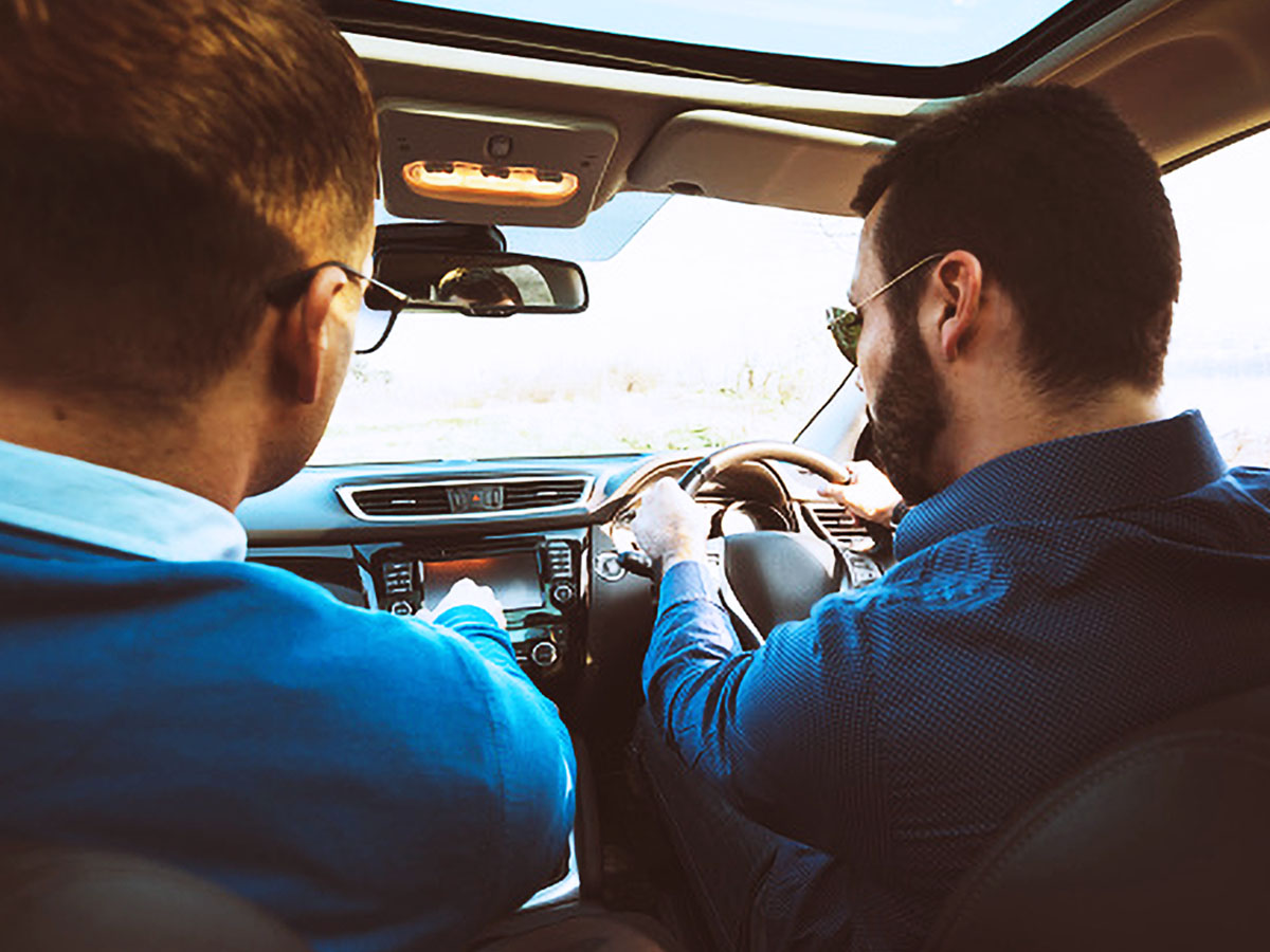 Two men in a car driving during the day, the picture is taken from behind them.