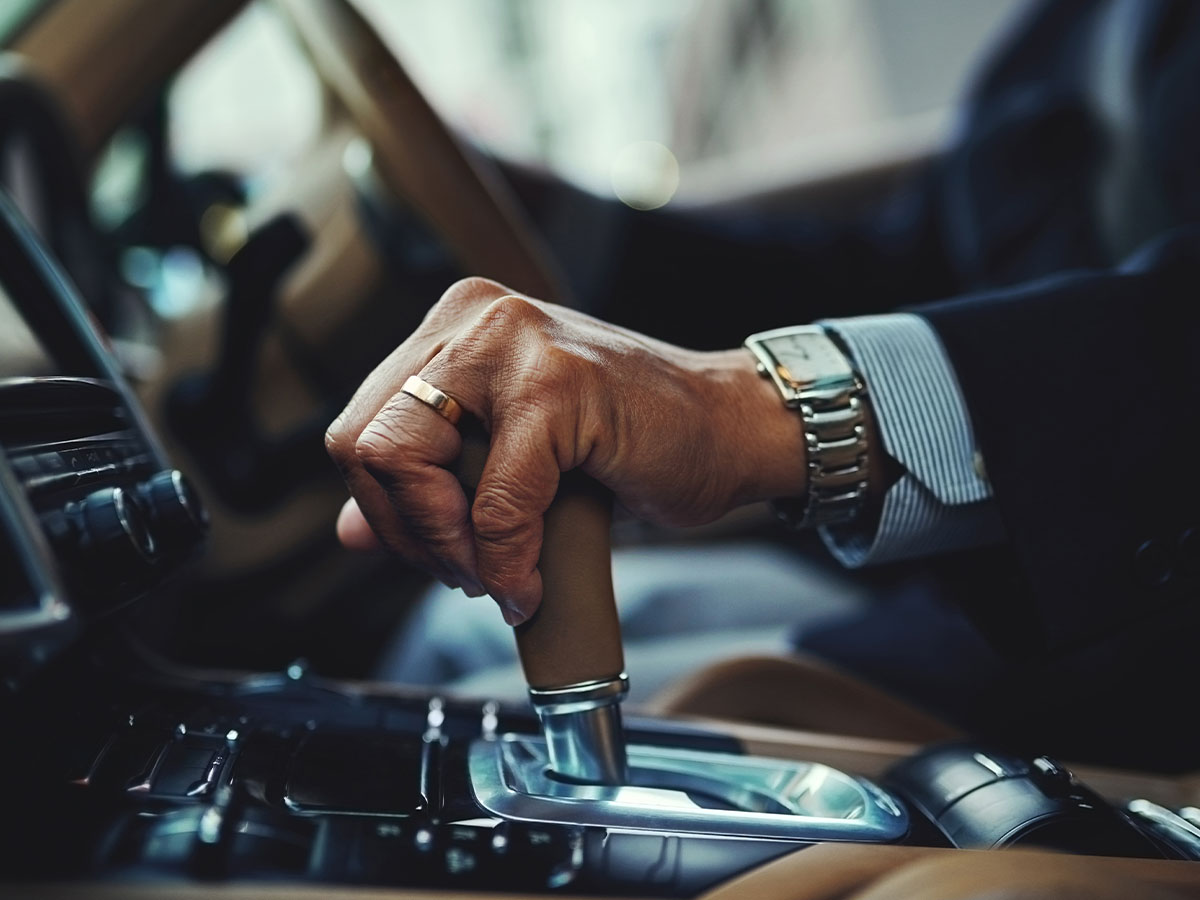 A person in a suit in a car with their hand with a watch and ring on holding onto the gear shifter of a car.
