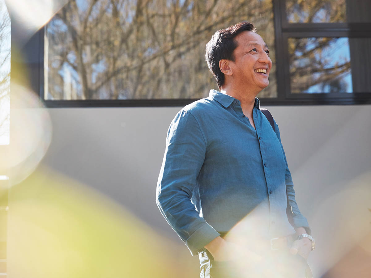Middle aged Asian man standing outside his home on a sunny day. Macquarie customer - Chi