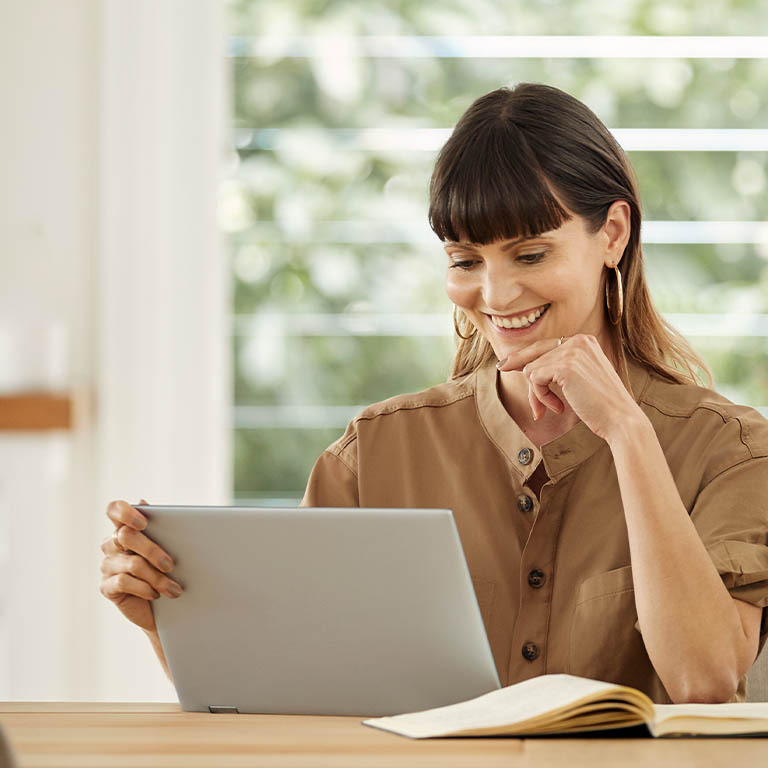 A woman with one hand on her face and the other holding a laptop screen, sitting at a wooden table in a dining room, well lit during the day.