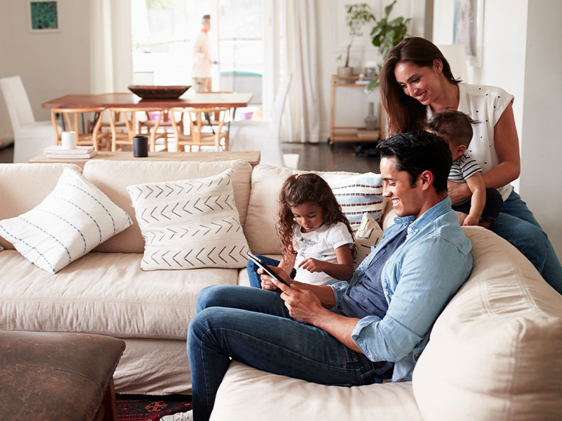 Young family sitting on sofa reading a tablet together in their living room